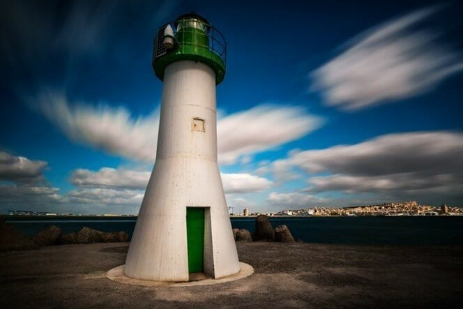 lighthouse green white blue sky clouds blur slow shutter speed