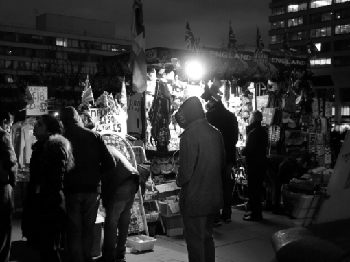 people in a busy night market looking at stalls black and white street photography portrait city people camera subject light how to tutorial guide