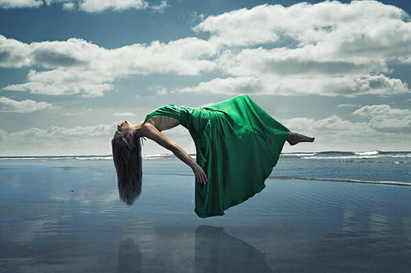 model photography floating over water in green dress