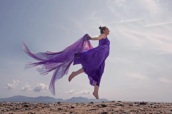 model floating purple dress beach