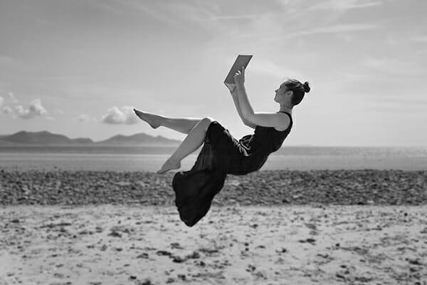 model floating on beach with a book in black and white