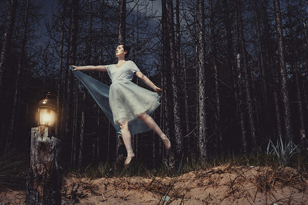 model floating in the woods with little lantern lighting the dark