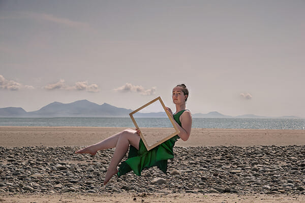 optical illusion model floating on beach with see through photo frame